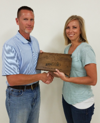 Darren Hamilton presents a plaque to outgoing school board member Tricia LeBrun for her 9 years of